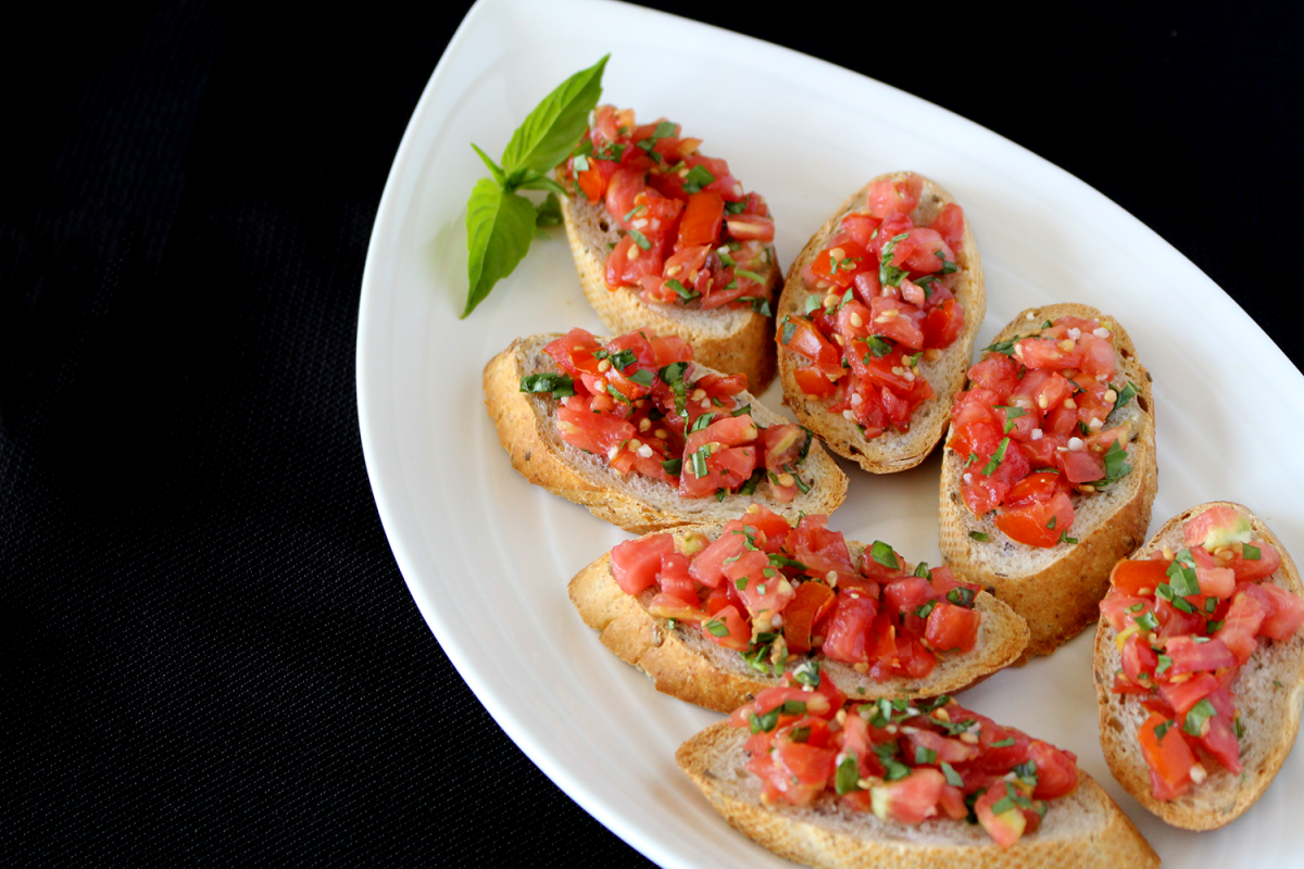 Bruschetta on an oblong plate with a black background. This quick-and-easy bruchetta recipe is sure to be a family favorite.