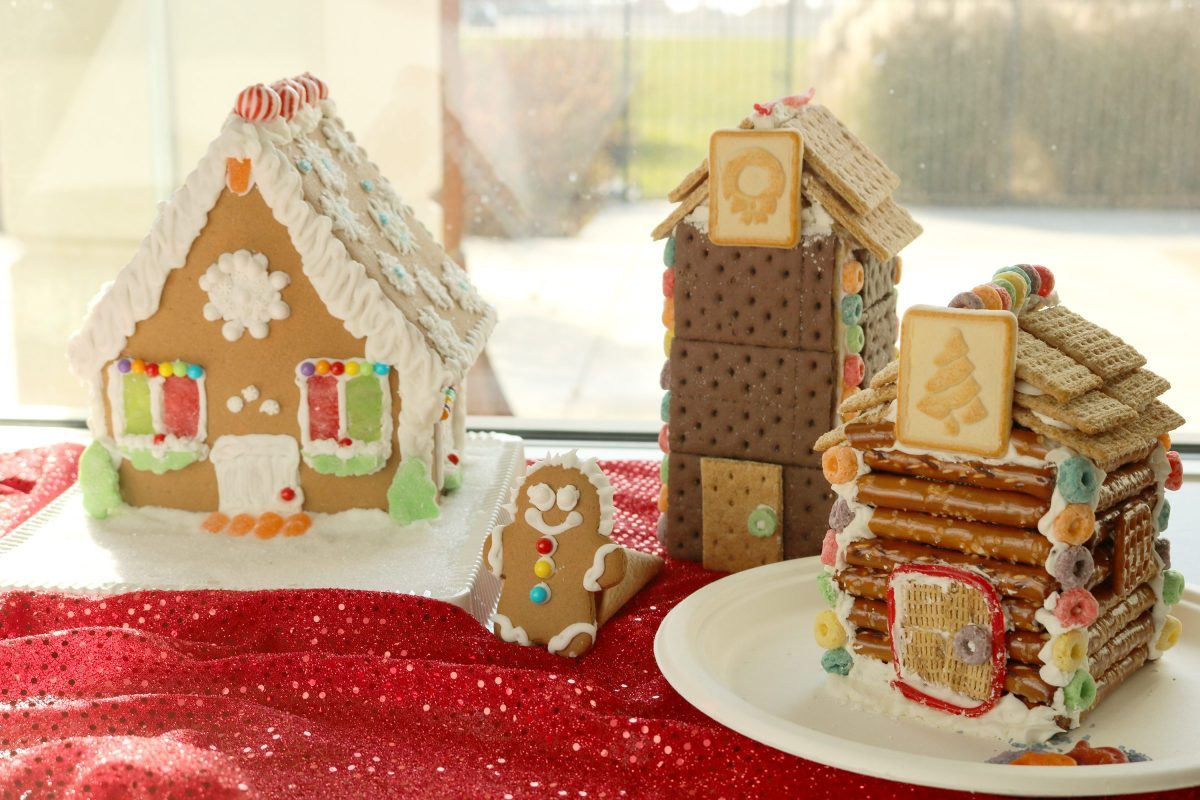 A Gingerbread house made with a kit, a clock tower made with graham crackers and a log cabin made with pretzel sticks