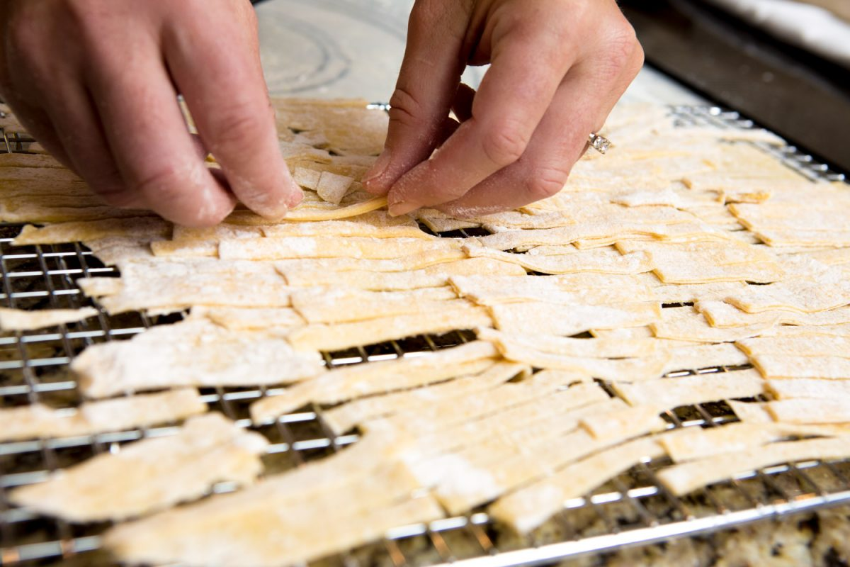 homemade egg noodles being placed on a cooking rack to dry