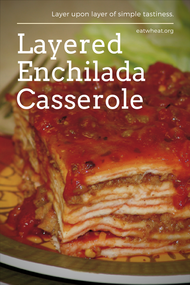 Layered enchilada casserole up close with gooey layers ready to eat