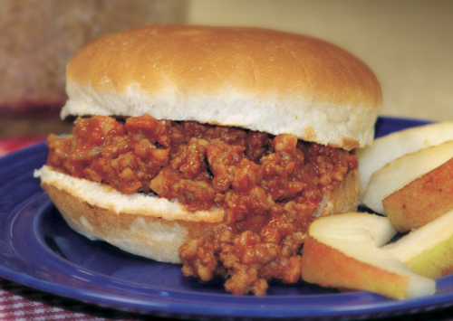 Sloppy Joes served with apples on a plate with a checkered table cloth