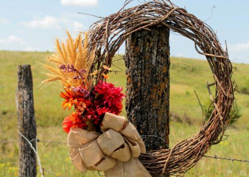 DIY Rustic Fall Wreath hung in front of a Kansas pasture