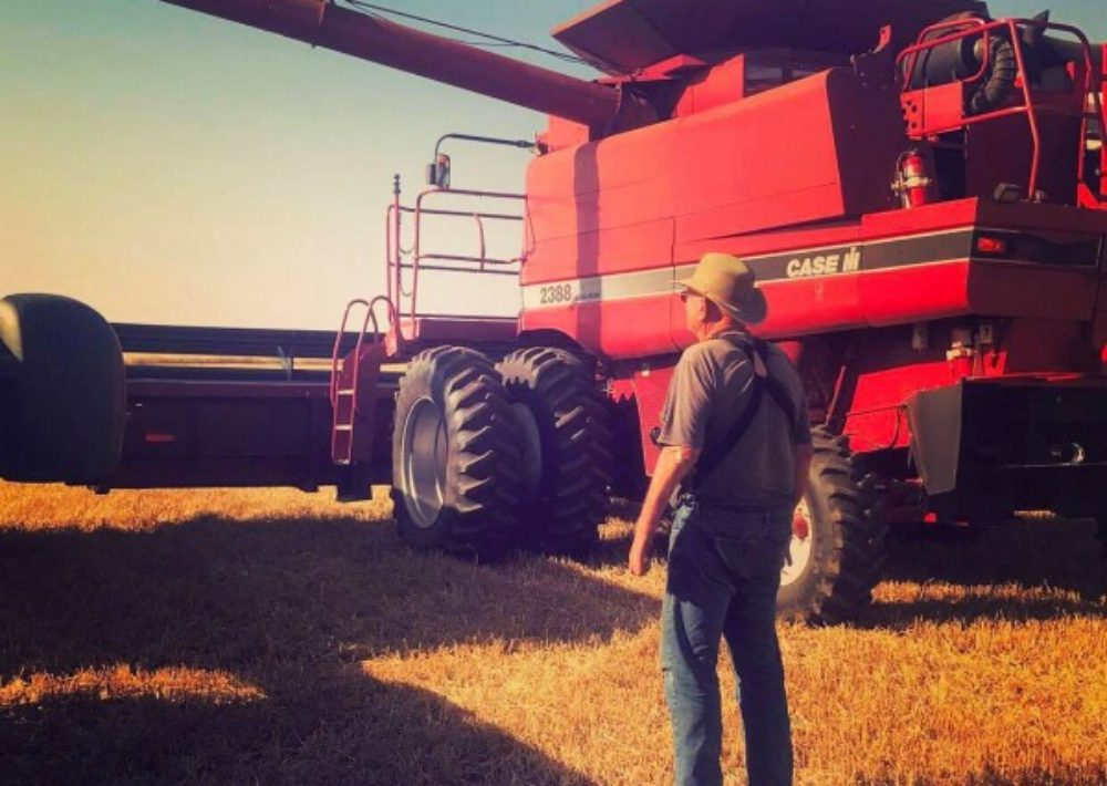 Mr. Westerman looks on as the family's wheat harvest continues on a beautiful day. His family has found the strength to fight cancer while remaining on the farm.