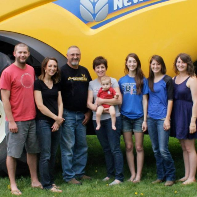 Happy farm family in front of combine.