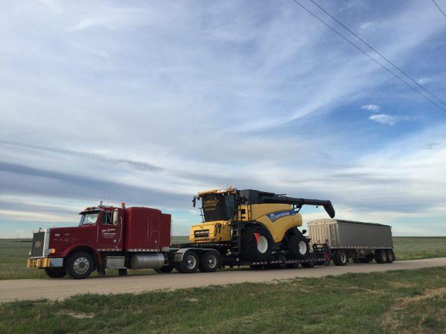 Semi truck hauling combine.