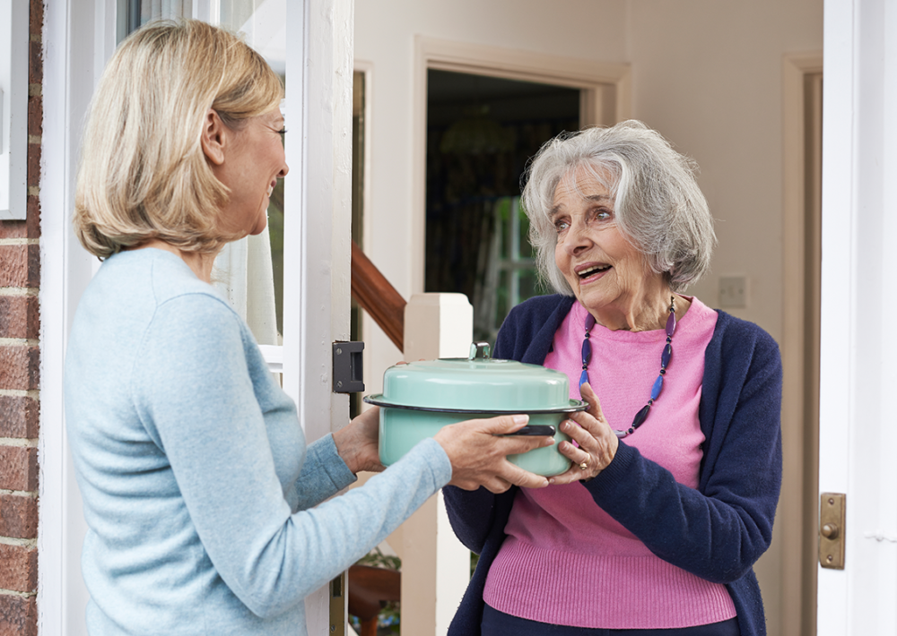 Photo: Woman delivering food to elderly neighbor.