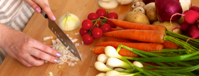 Photo: Hands chopping vegetables with knife.