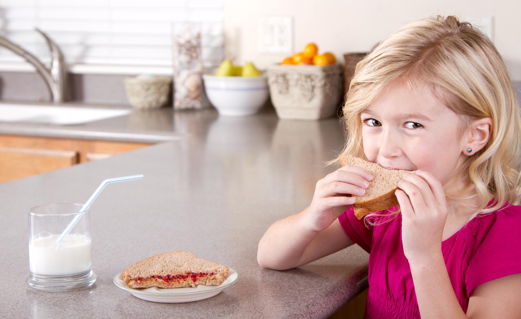 Photo: Girl eating whole grain sandwich.