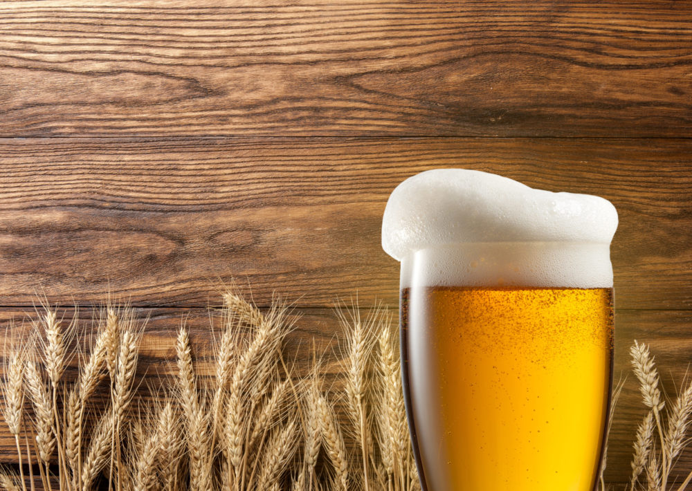 Wheat beer in front of wheat and wood background