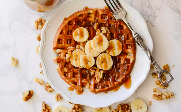 Banana Bread Waffles with Brown Sugar Caramel Syrup on a white plate with a fork. This is one of our unique waffle recipes