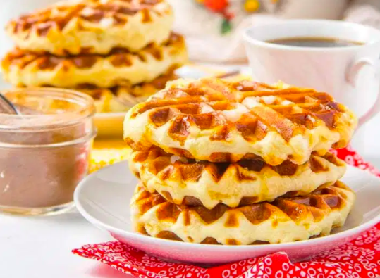 Three belgian waffles on white plate with waffles, coffee and drizzle in the background. Unique Waffle Recipe