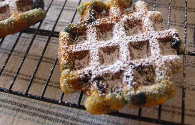 Blueberry Muffles dusted with powdered sugar on a wire cooling rack