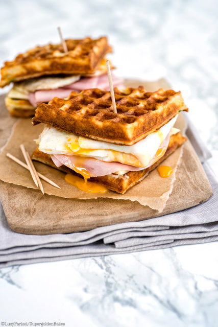 PARMESAN WAFFLE, HAM, CHEESE AND EGG BREAKFAST SANDWICH on a cutting board
