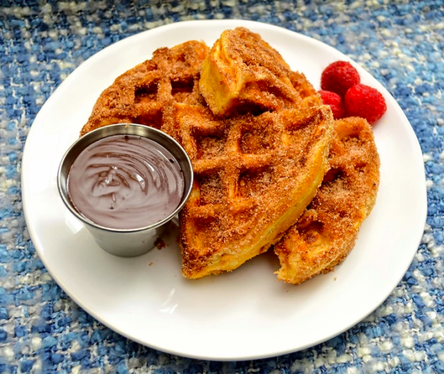 Churro Belgian Waffles with Mexican Chocolate Sauce on white plate garnished with raspberries