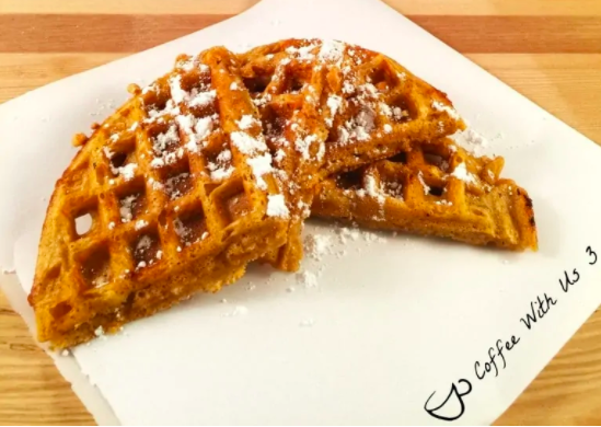 Sweet potato waffles with powdered sugar on parchment paper