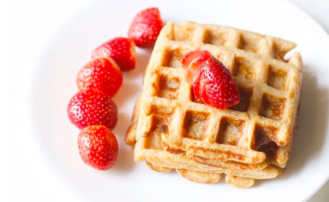 Whole Wheat Waffles on a white plate topped with strawberries