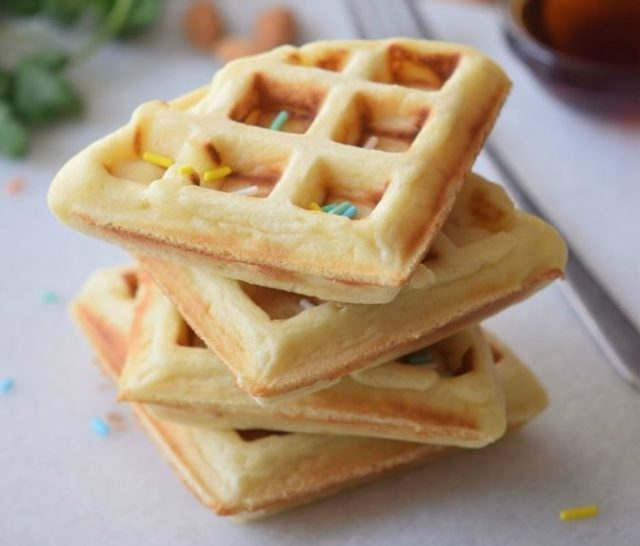 Cake waffles topped with sprinkles on a white cutting board