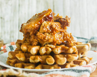 Fried chicken on top of waffles being drizzled with maple syrup. This is one of our unique waffle recipes