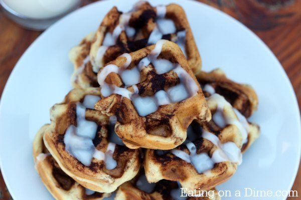 Cinnamon Roll Waffles drizzled with frosting on a white plate. One of our 18 unique waffle recipes