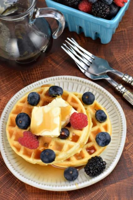 Classic Waffles topped with syrup, butter and berries on a white plat with two forks in the background