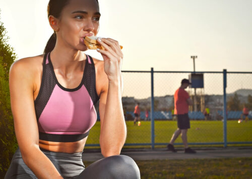 Image: Woman athlete eating sandwich after workout.
